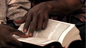 Um homem segurando a Bíblia Yalunka.